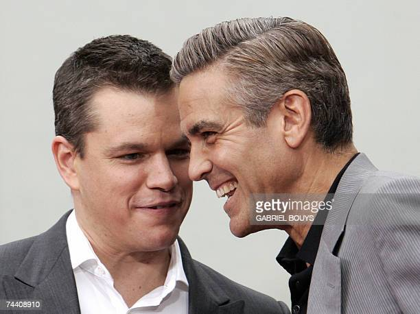 Actors Matt Damon and George Clooney share a joke after immortalizing their prints in cement in the famed forecourt of Graumans Chinese Theatre in...