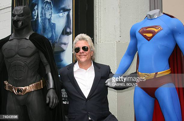 Hollywood, UNITED STATES: Hairdresser and film producer Jon Peters poses with Batman and Superman characters after being honored with a star on the...