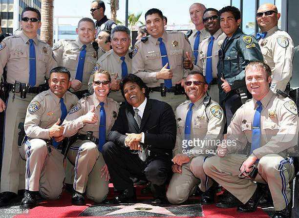 US actor Erik Estrada poses with California Highway Patrol Police officers after he was honored with a Star on the Hollywood Walk of Fame on...