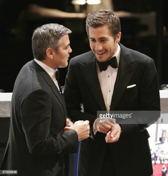 US actors George Clooney and Jake Gyllenhaal speak before the start of the 78th Academy Awards ceremony in Hollywood 05 March 2006 Clooney is...