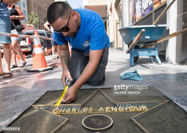 TOPSHOT Hollywood Walk of Fame Starmaker Vince Godinez prepares Charles Aznavour's star in front of the Pantages on August 21 in Hollywood California...