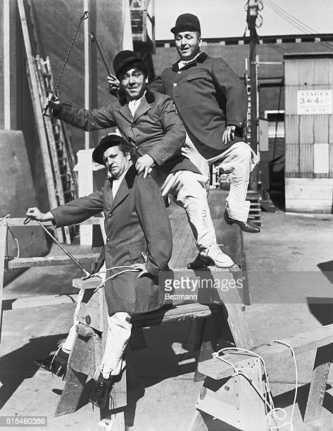 Hollywood's Stooges seem to be under the cowboy influence as they go 'riding' around the set Top to Bottom Jerry Howard Moe Howard and Larry Fine