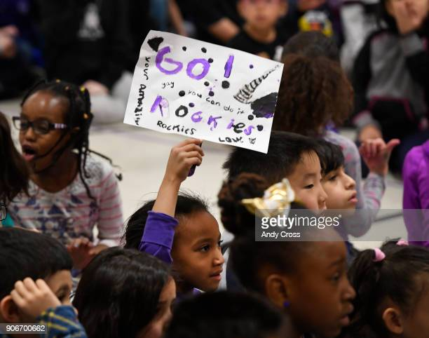 Holm Elementary School 1st grader Luna Tesfay holds a handmade sign showing her support for the Colorado Rockies Caravan Make an Impact rally at the...