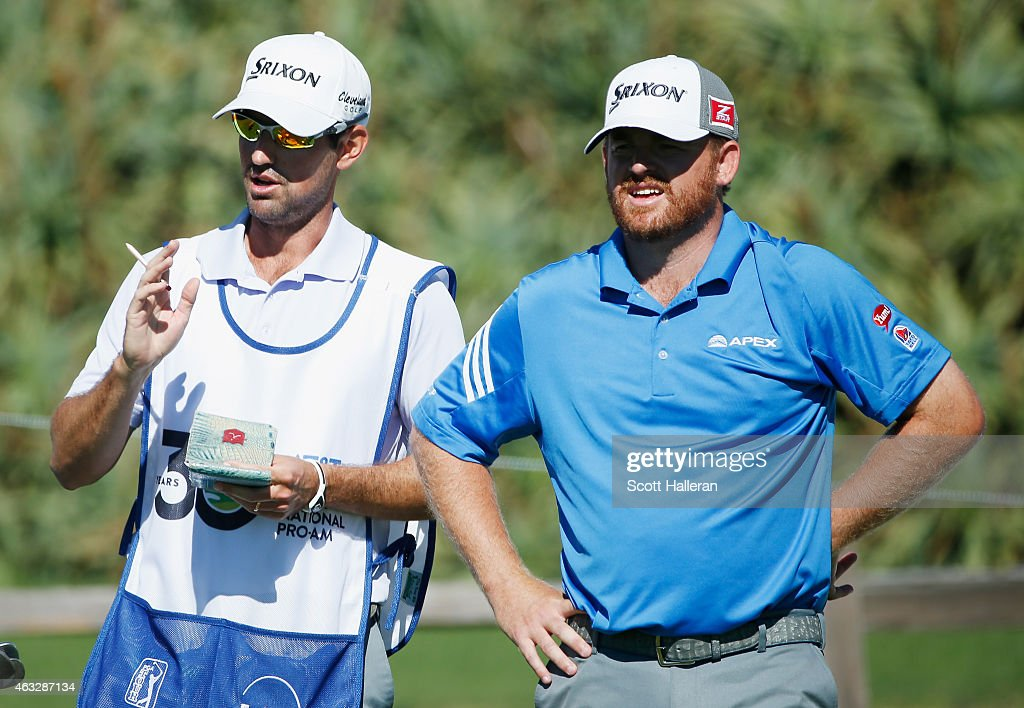 J. B. Holmes chats with his caddie Brandon Parsons on the sixth tee during the first round of the AT&T Pebble Beach National Pro-Am at the Pebble Beach Golf Links on February 12, 2015 in Pebble Beach, California.