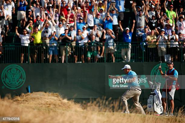 B Holmes of the United States celebrates after holing out for eagle on the 16th hole during the third round of the 115th US Open Championship at...