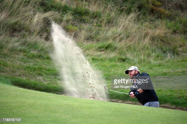 B Holmes of the United States hits his third shot from the bunker on the seventh hole during the third round of the 148th Open Championship held on...