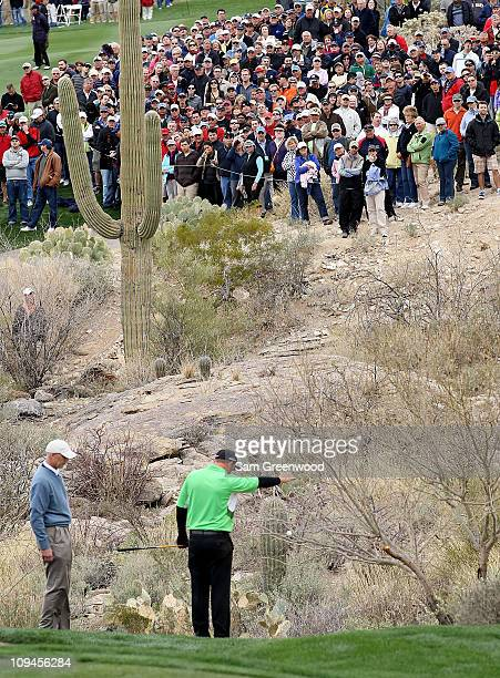B Holmes takes a drop off the 18th green in front of a gallery of fans during the quarterfinal round of the Accenture Match Play Championship at the...