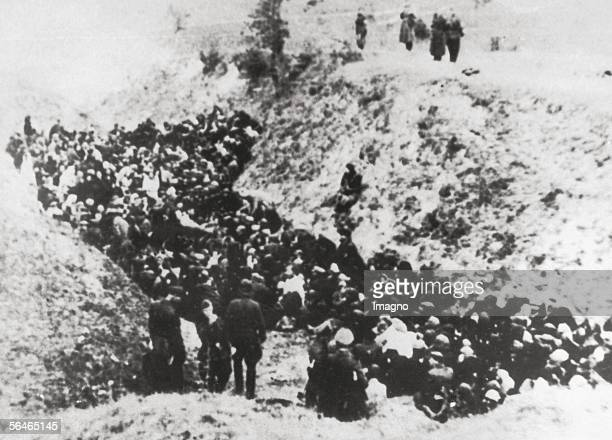 Holocaust: Polish Jews before execution are guarded by german soldiers next to a ditch. Belzec or Sobibor. Around 1941. Photograph. [Holocaust:...
