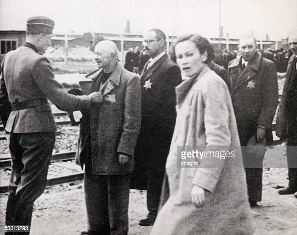 Holocaust Selection at extermination camp Auschwitz on the left German soldier with rows of men with Yellow Stars on their coats in the front woman...