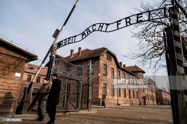 "Holocaust survivor and former prisoner of the Nazi death camp Auschwitz-Birkenau, Johnny Jablon , crosses the gate with the inscription reading ""Work..."