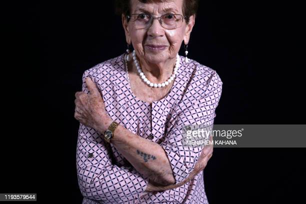 Holocaust survivor Batcheva Dagan whose entire family was killed poses while showing her arm with the Auschwitz prison number 45554 during a photo...