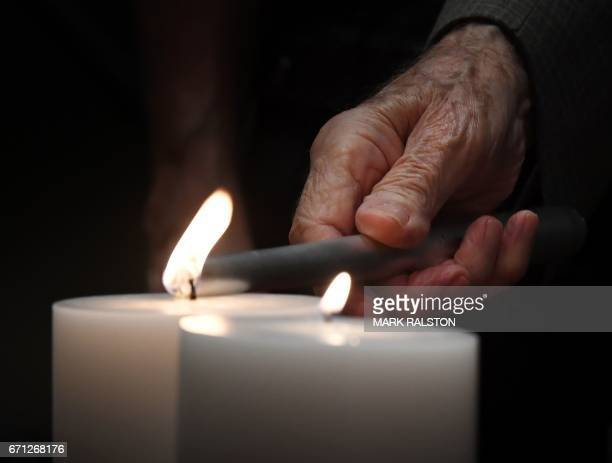 Holocaust survivor Charles Selarsz lights a candle in memory of the 6 million Jews who died under the Nazi regime during a Holocaust Memorial Day...