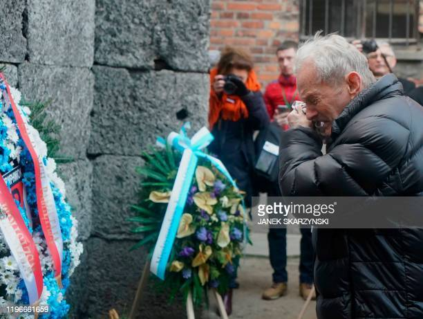 A Holocaust survivor cries as he pays his respect at the death wall at the memorial site of the former German Nazi death camp Auschwitz during...