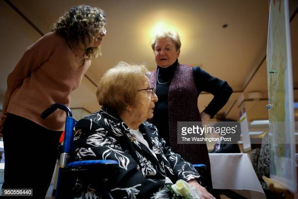 Holocaust survivor Fanny Aizenberg center accompanied by her daughter Josiane Trum looks a map that shows where other survivors were born during the...