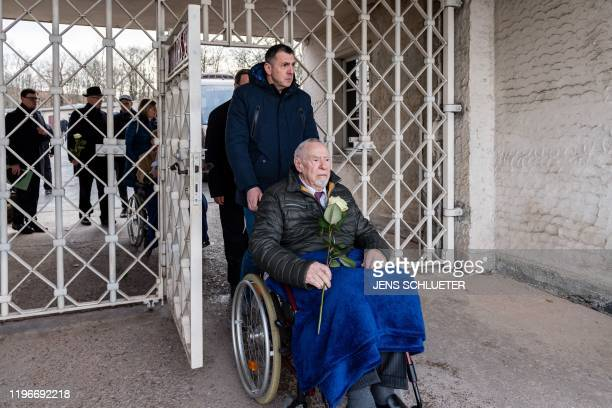 """Holocaust survivor Guenter Pappenheim sits in a wheelchair as he arrives through the main gate with the inscription """"Jedem das Seine"""" at the memorial..."""
