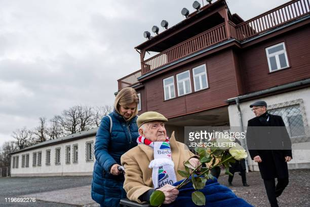 Holocaust survivor Heinrich Rotmensch sits in a wheelchair as he arrives to attend a ceremony at the memorial site of the former Nazi concentration...