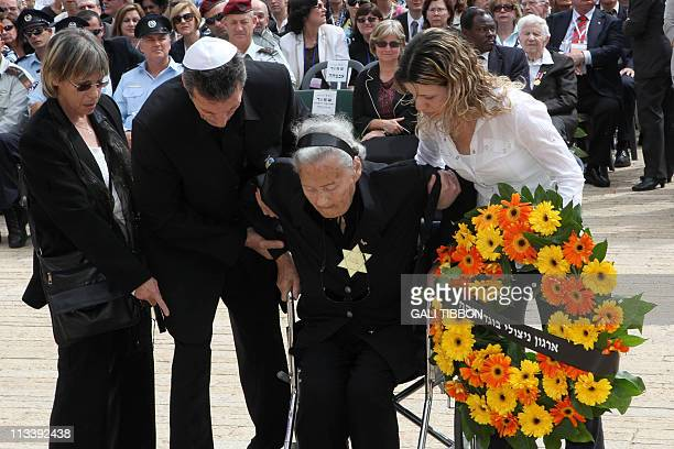 A holocaust survivor of the Bogdanovka concentration camp wears the Star of David with 'Jude' German for Jew written on it as she is helped from her...
