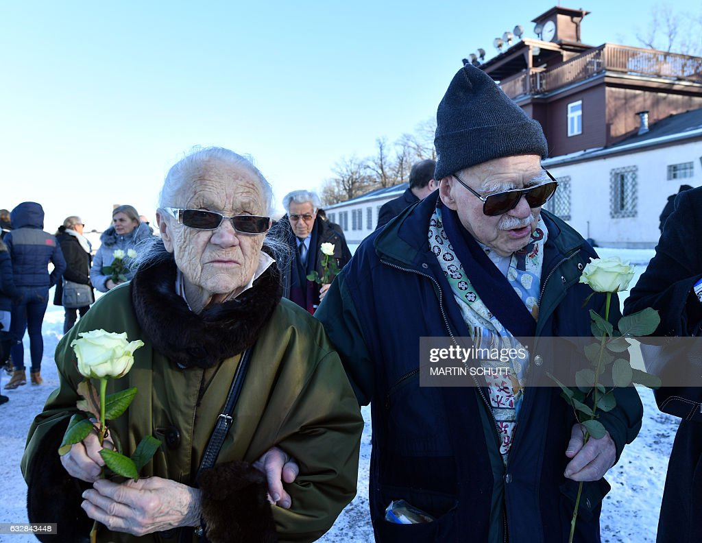 Holocaust survivor Pavel Kohn (R) and his wife Rut Kohn arrive to place flowers at the former Buchenwald Nazi concentration camp near Weimar, eastern Germany, on January 27, 2017, during the International Holocaust Remembrance Day. / AFP / dpa / Martin Schutt / Germany OUT