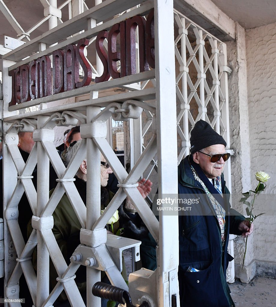 Holocaust survivor Pavel Kohn (R) walks through a gate with the inscription 'Jedem das Seine' (to each his own) as he arrives to place flowers at the former Buchenwald Nazi concentration camp near Weimar, eastern Germany, on January 27, 2017, during the International Holocaust Remembrance Day. / AFP / dpa / Martin Schutt / Germany OUT