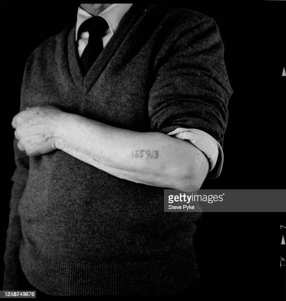 Holocaust survivor, Sam Piunik, showing the tattoo of his prisoner identification number on his left forearm, London, 1995. Piunik was a prisoner at...