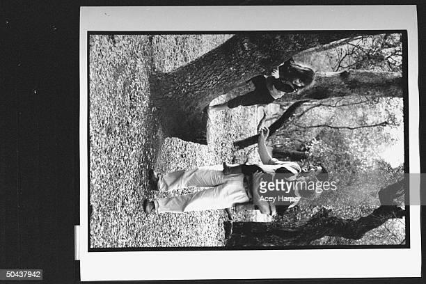 Holocaust survivor Zev Kedem aka Zbigniew Wohlfeiler holding son Adam while daughter Katia climbs tree in park; he was at Oskar Schindler's factory...