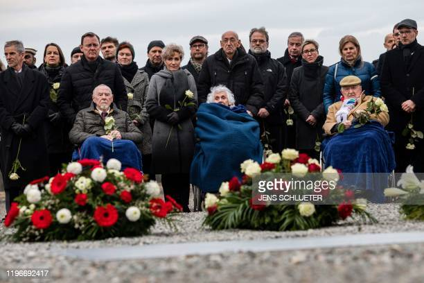 Holocaust survivors Guenter Pappenheim, Eva Fahidi-Pusztai and Heinrich Rotmensch sit in wheelchairs as they attend a ceremony at the memorial site...