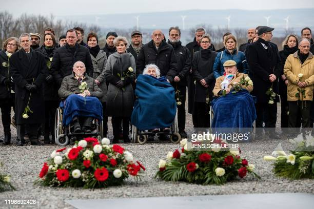 Holocaust survivors Guenter Pappenheim Eva FahidiPusztai and Heinrich Rotmensch sit in wheelchairs as they attend a ceremony at the memorial site of...