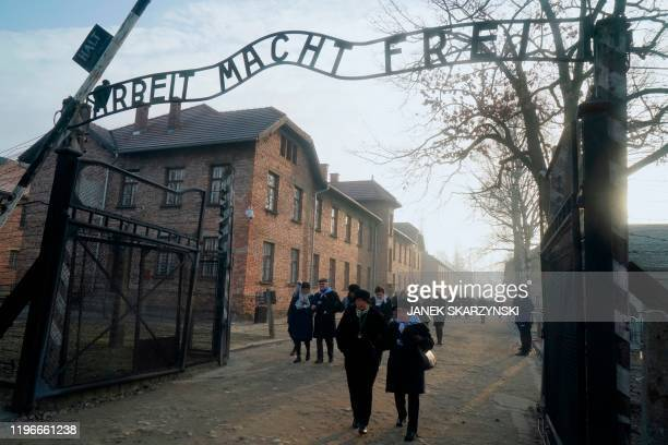 "Holocaust survivors walk below the gate with its inscription ""Work sets you free"" after a wreath laying at the death wall at the memorial site of the..."