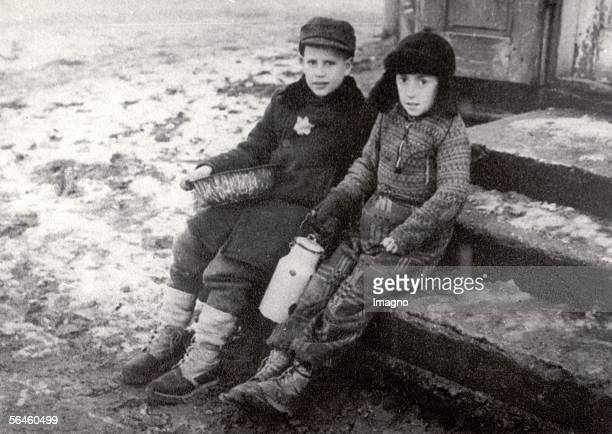 Holocaust Two children in the snow covered Ghetto of Warsaw one boy with Yellow Star on the coat and bowl the other with milk can Photography About...