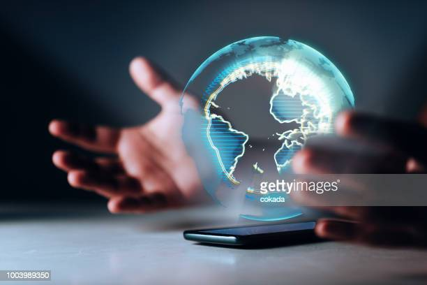 holographic earth on smartphone - big tech stock pictures, royalty-free photos & images