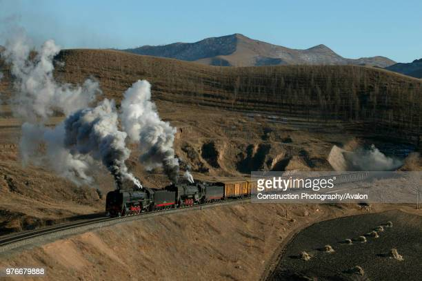 A Holoku to Daban freight headed by two former China Railway QJ Class 2102s emerges from tunnel number four on the Jing Peng pass section of the...