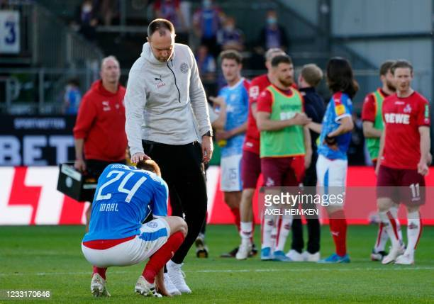 Holstein Kiel's German defender Hauke Wahl is comforted by Holstein Kiel's German head coach Ole Werner after the German second leg play-off...