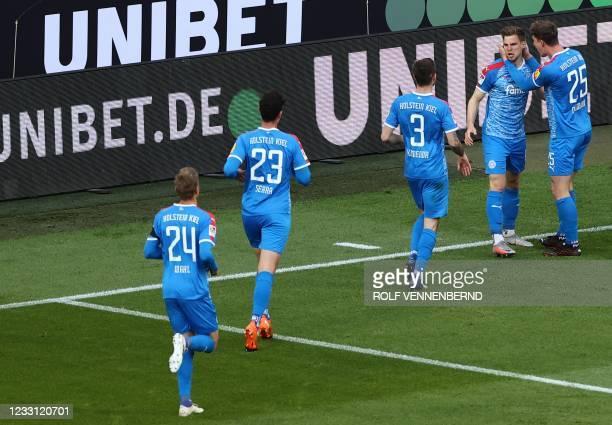 Holstein Kiel's German defender Simon Lorenz celebrates with team mates scoring the 0-1 during the German relegation Bundesliga football match...