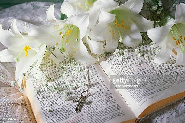 holy bible, white lilies and cross - crosses with flowers stock pictures, royalty-free photos & images