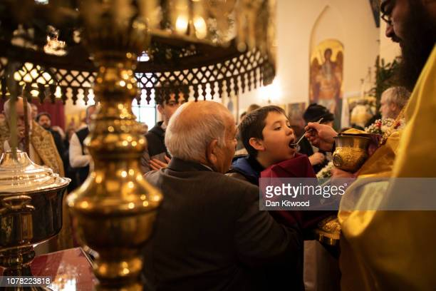 Holy Communion is received as Archbishop of Thyteiri and Great Britain blesses parishioners and clergy of the Greek Orthodox Church of St Michael the...