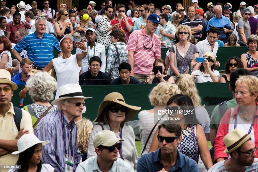 Holy Fisher of Great Britain serves against Mai Hontama of Japan as spectators follow the action around the oudide courts on day six of the Wimbledon Lawn Tennis Championships at the All England Lawn Tennis and Croquet Club on July 8, 2017 in London, England.