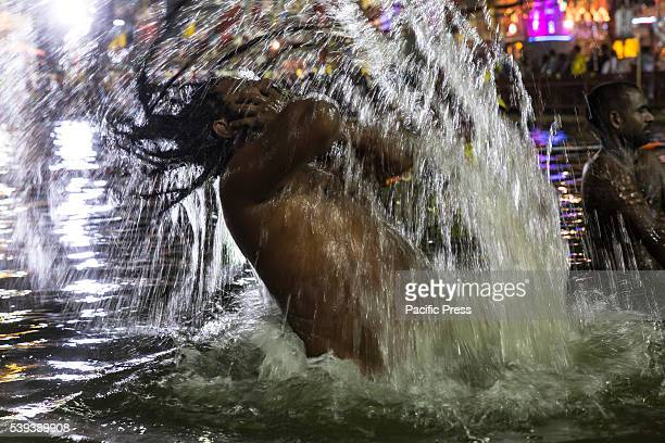 Holy Hindu Monk is playing with his dreadlocks while taking the holy dip early morning on the bank of sacred river Shipra, also known as Kshipra on...