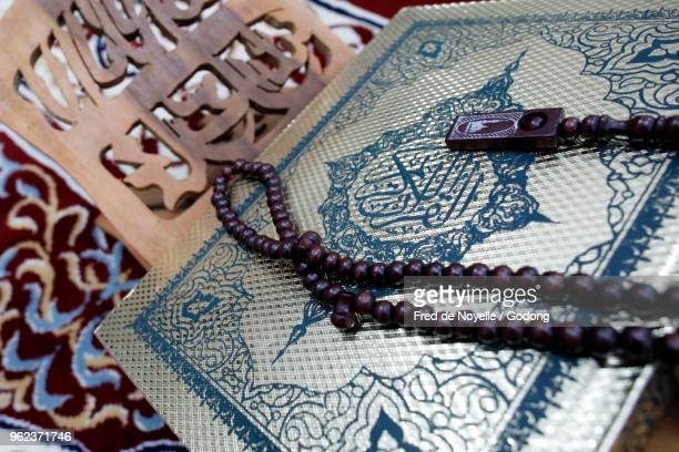 holy quran and muslim prayer beads on wood stand. - allah photos et images de collection