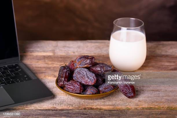 holy ramadan concept. copper plate with dates, glass of milk near the laptop. - written date stock pictures, royalty-free photos & images
