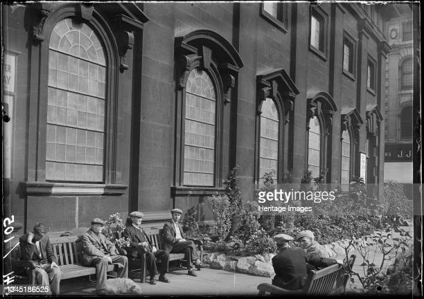 Holy Trinity Church, Boar Lane, Leeds, 1941. An exterior view of the Holy Trinity Church, showing the south front with men sat on benches in the...