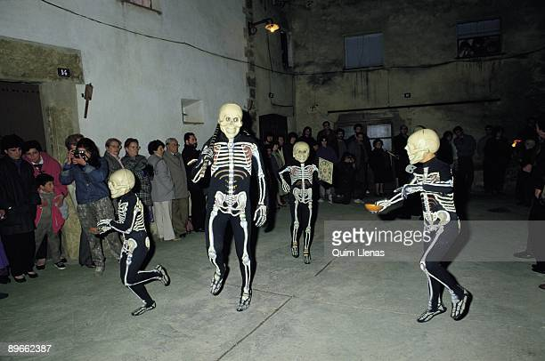 Holy Week in Verges Gerona An adult and three children disguised of skeletons dance in a square of the town of Verges