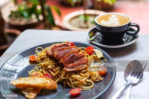 ホマメイドスモークダックスパゲッティアリオエオリオはダイニングテーブルで提供 - 鴨肉 ストックフォトと画像