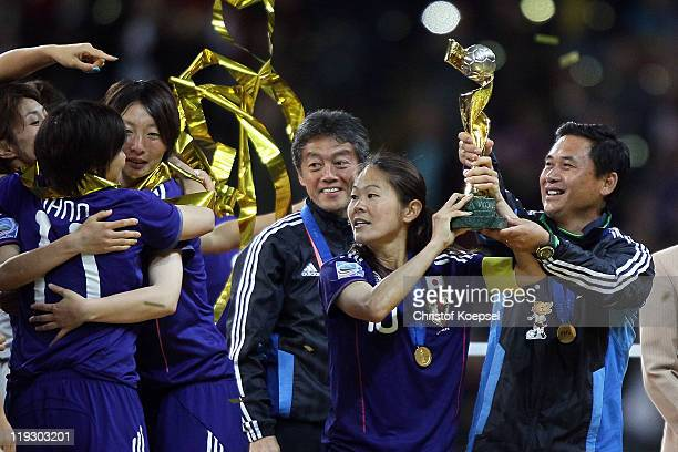 Homare Sawa of Japan and Head coach Norio Sasaki of Japan lift the winning trophy on the podium after winning 53 after penalyts shootout the FIFA...