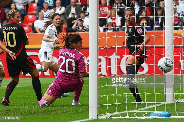 Homare Sawa of Japan scores her team's third goal against Dinora Garza goalkeeper Cecilia Santiago and Veronica Perez of Mexico during the FIFA...