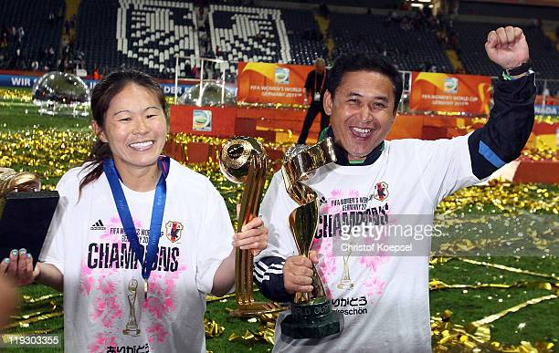 Homare Sawa presents the adidas golden ball trophy for the best player of the tournament and head coach Norio Sasaki of Japan lifts the Women's World...