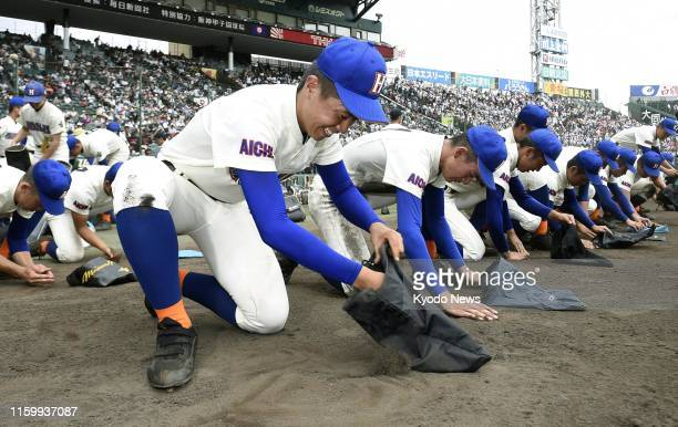 Homare team members collect dirt after losing in the first round of the national high school baseball tournament at Koshien Stadium in Nishinomiya,...