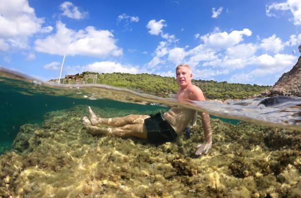 Hombre joven disfruta de un dia de playa sentado sobre una roca bajo el agua en una cala de la isla de Menorca