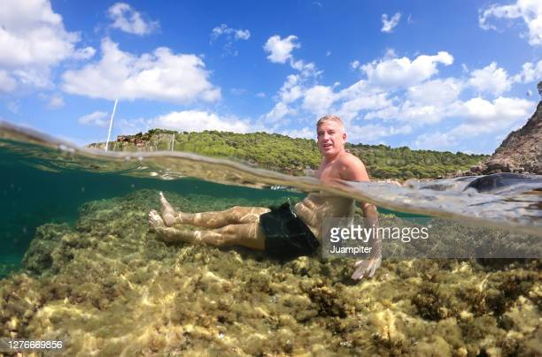 hombre joven disfruta de un dia de playa sentado sobre una roca bajo el agua en una cala de la isla de menorca - aktiver lebensstil stock-fotos und bilder