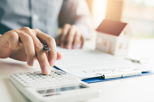 Home agents are using a calculator to calculate the loan period each month for the customer. 1075993466