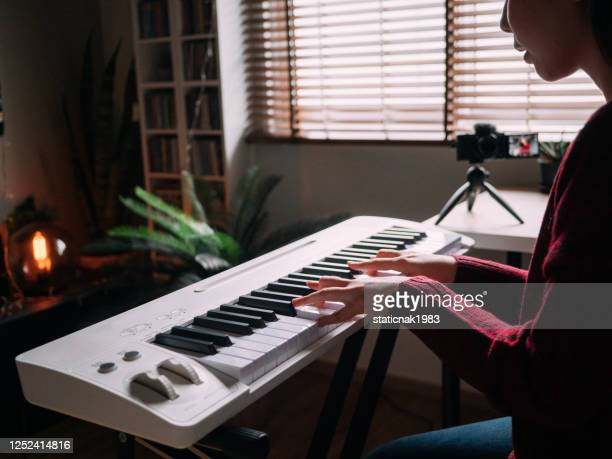 home alone keyboard piano hobby young woman practicing piano with smartphone - keyboard player stock pictures, royalty-free photos & images